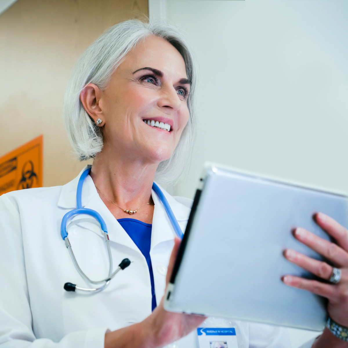 smiling female doctor looking at notes on a clipboard