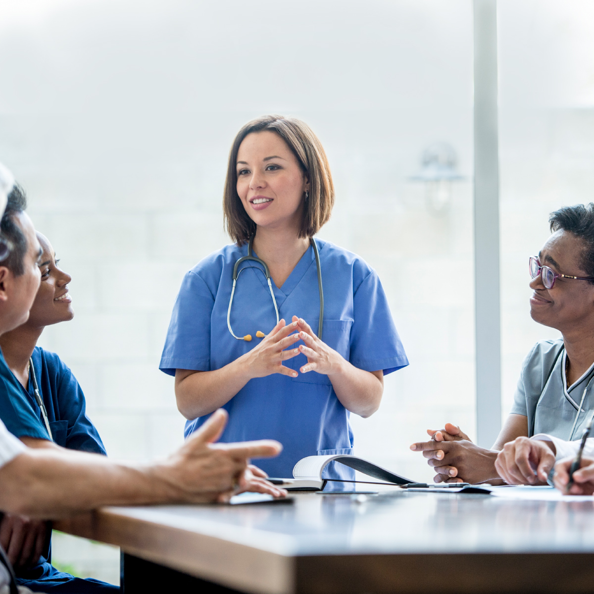 smiling female doctor addressing other doctors around a table