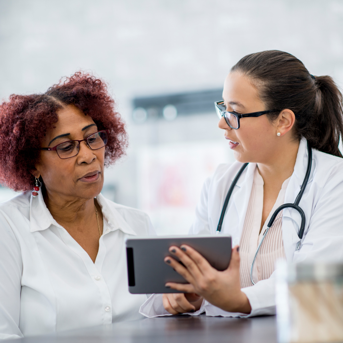 female doctors discussing notes on a tablet with female patient