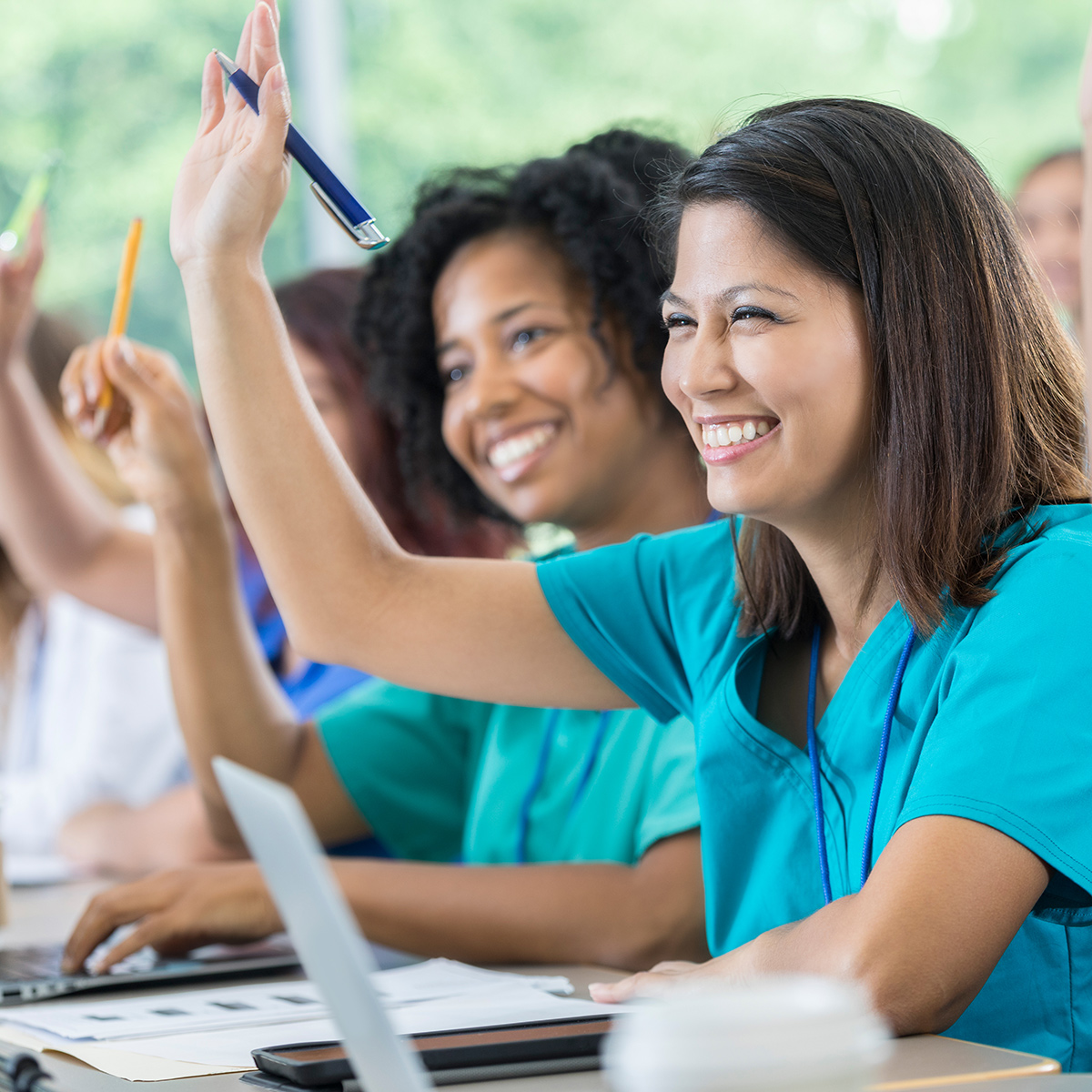 smiling women in scrubs in classroom setting, raising hands