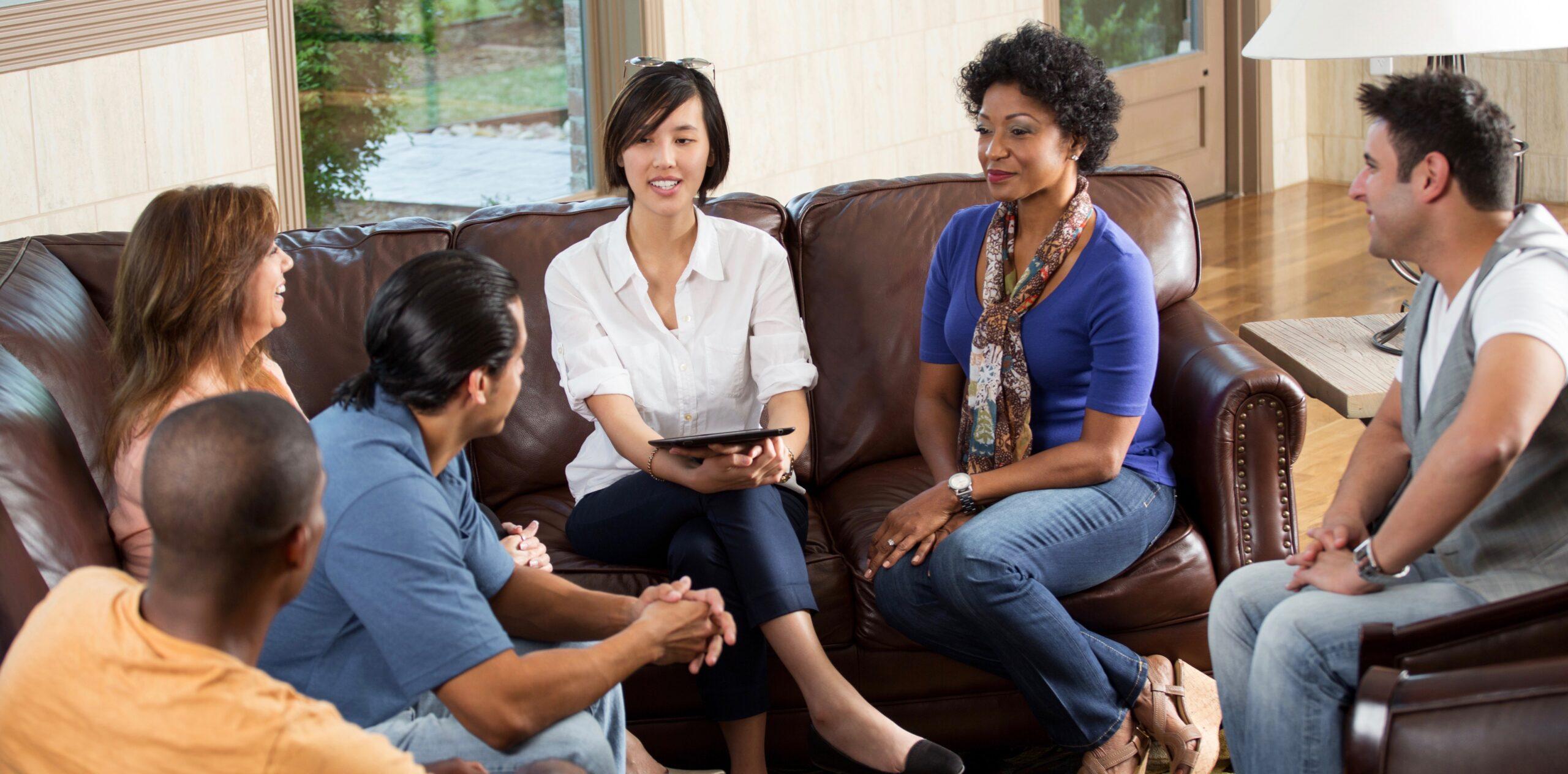 Three medical professionals examine a clipboard
